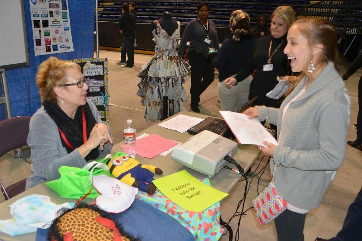 Cypress Falls High School junior Emily Hernandez speaks with Cypress Falls fashion design and interior design teacher Amanda Bailey about the school's program during the Career Options Fair at the Berry Center on Dec. 2.