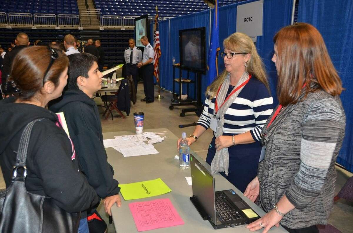 Career technology education teachers Meg Young of Jersey Village High School and Keren Grissom of Langham Creek High School discuss secondary options with Salyards Middle School eighth-grade student Daniel Garcia and his mother, Ana Garcia, at the Career Options Fair.