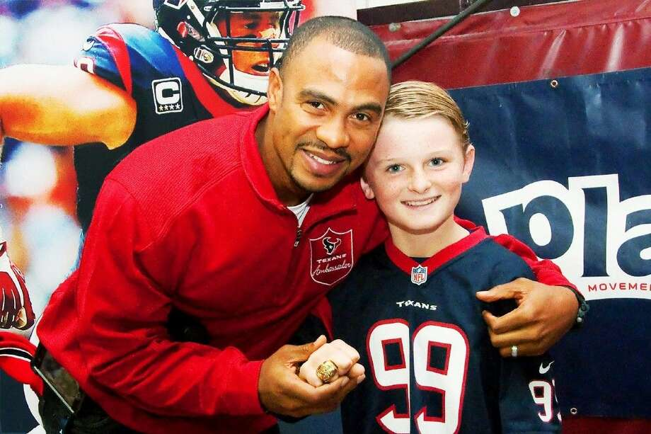 Magnolia Elementry student Jackson Blank tries on Former Houston Texan Eric Brown's Super Bowl ring. Brown won the ring while playing with the Denver Broncos. The former Texans visited as part of the Houston Texans Gatorade Junior Training Camp.