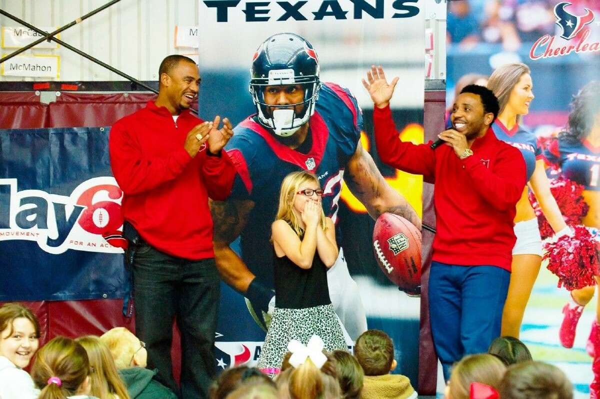Former Texans Eric Brown and J.J. Moses quiz Magnolia Elementary student Alexis Mantleon on Texans Football history to win at Texans t-shirt.