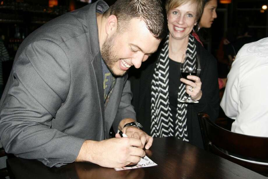 """Kingwood resident Hunter Larsen signs autographs at the premiere party for the reality show he is a part of called """"Redneck Island"""" at the Tasting Room Kingwood on Thursday, Dec. 4, 2014."""
