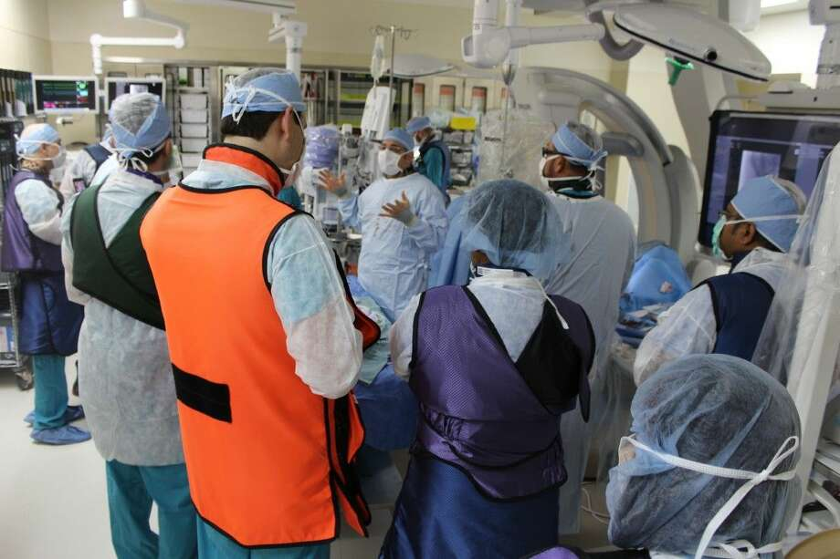 The advanced technology in the hybrid endovascular surgical suite at Memorial Hermann Northeast Hospital has helped thousands of area residents and has made it an ideal learning site for surgeons from across the state and country since it opened in February. Kousta Foteh, M.D. (center), a vascular surgeon affiliated with the hospital, explains the pedal access technique to visiting surgeons in the surgical suite.