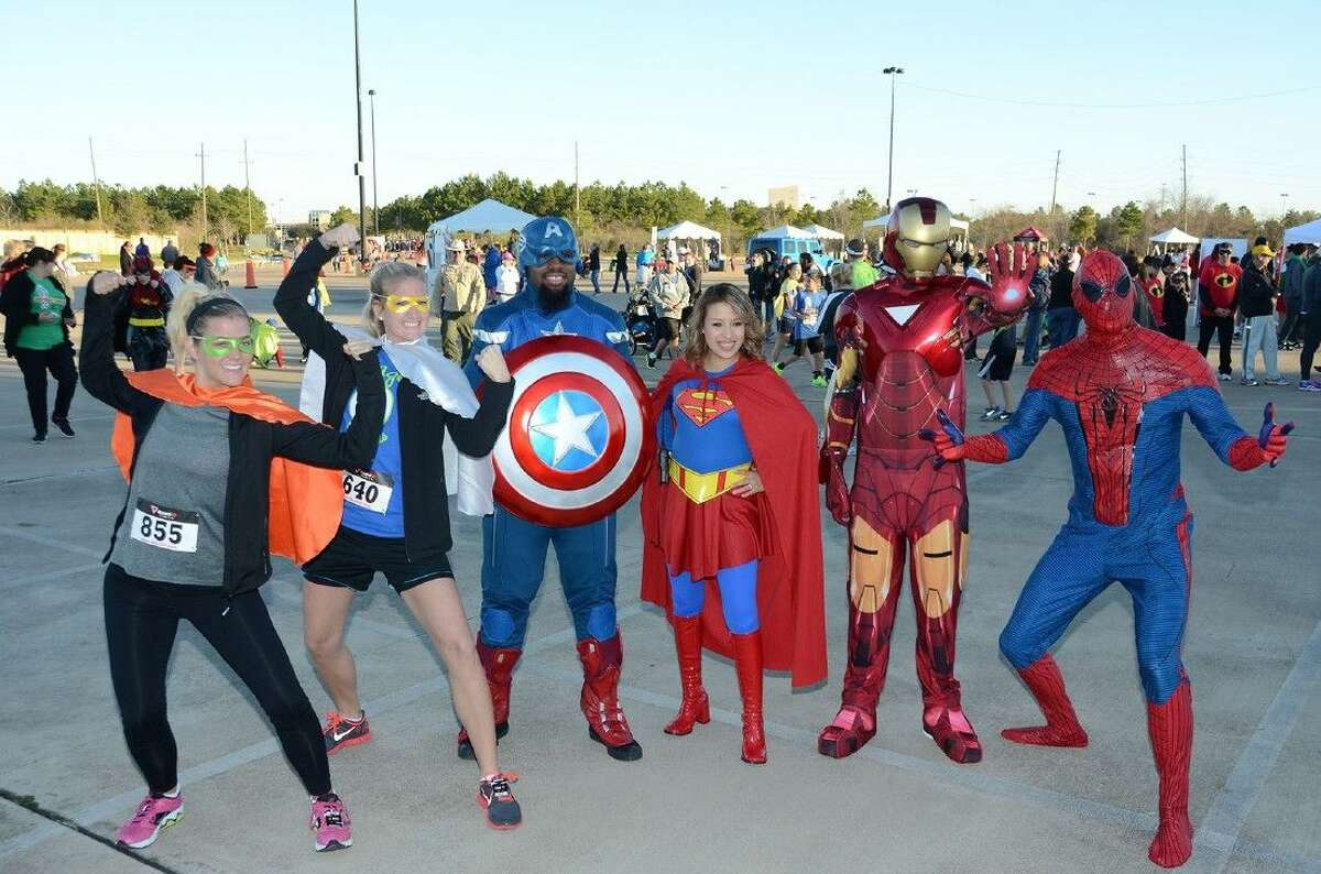 Participants in the inaugural Superintendent Fun Run pose with live-action superheroes during the 2014 event. Additional superheroes such as Superman, Batman and Lady Hawk will join the 2015 event on Feb. 21.
