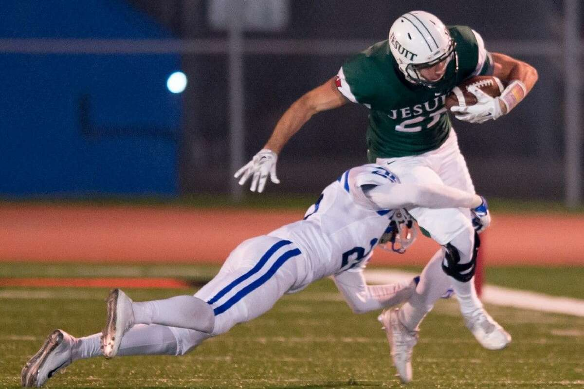 A Strake Jesuit ballcarrier tries to get away from a Cy Creek defending during the schools' Division II, Region III-6A Area Round playoff matchup Friday night at Crusader Stadium, which Jesuit won 44-28 to advance to this week's regional semifinal against Manvel.