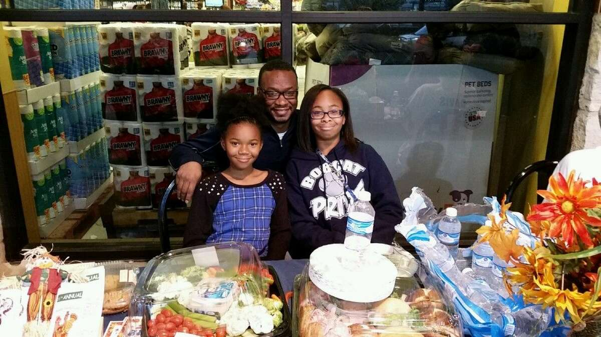 Sammy Davis and his two daughters, Jaylah and Taylor, during the sixth annual Bird Bowl and HAAM food drive at the Atascocita Kroger Tuesday, Nov. 24, 2015. Davis partnered with HAAM and Kroger to give 50 families a full Thanksgiving meal.