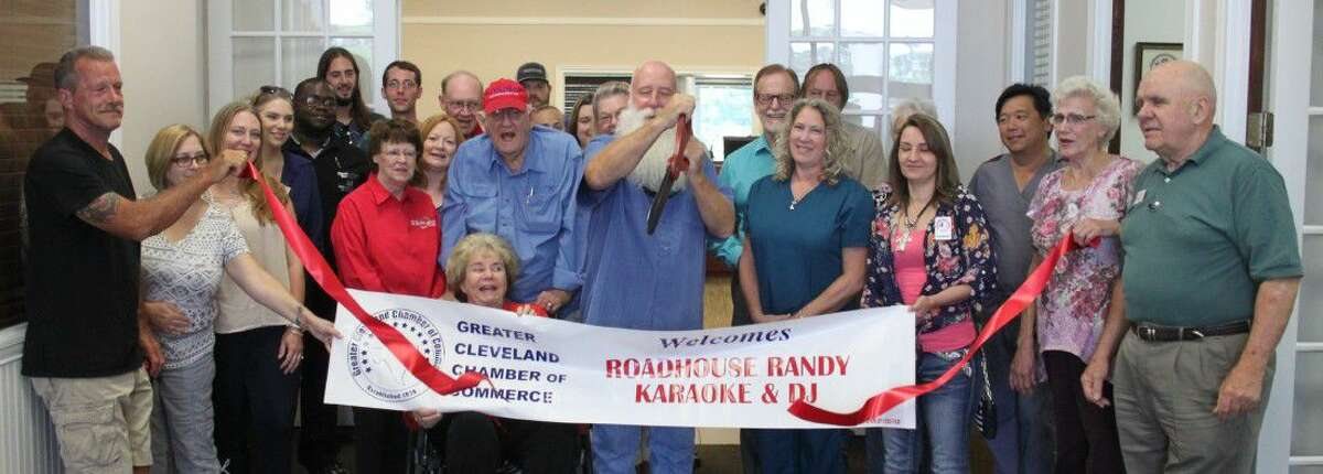 Randy Peery cuts the ribbon to symbolize his welcoming into the Greater Cleveland Chamber of Commerce at the Chamber's office on June 28. Peery is the owner of Roudhouse Randy Karaoke and DJ.