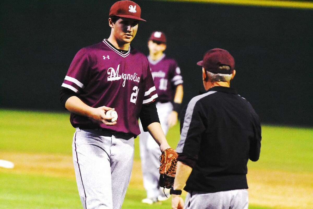 Magnolia's Adam Kloffenstein hands the baseball to coach Dale Westmoreland this past season. Westmoreland shared District 19-5A co-Coach of the Year honors with Tomball's Doug Rush.