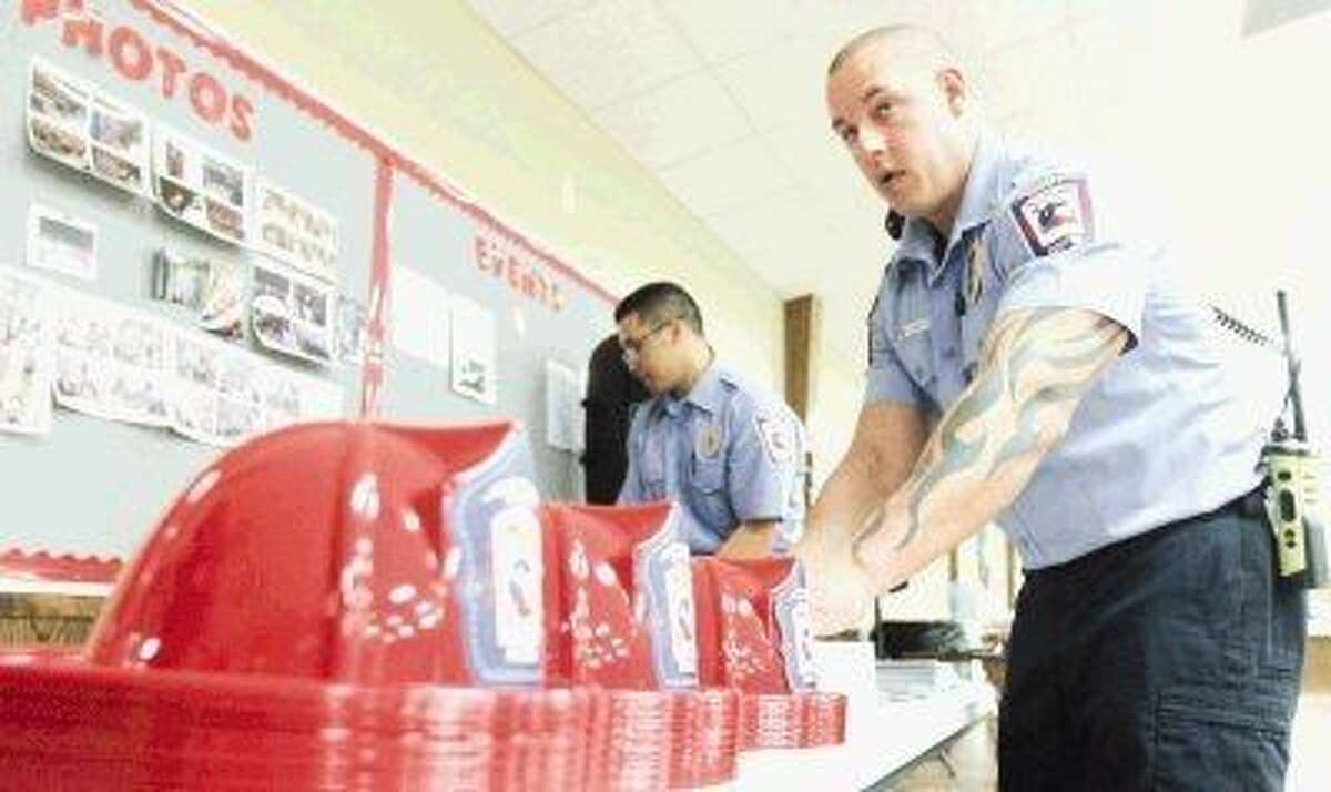 Porter firefighter Jeremy Watts arranges firefighter hats during Saturday's fundraiser at Bull Sallas Park Friendship Center in New Caney.