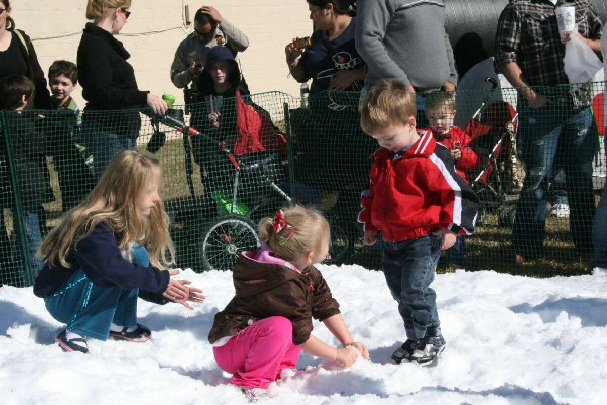 Children bound along joyfully in the snow pit at the 2014 Old Fashioned Christmas event in downtown Katy. The event will feature the snow pit, writing letters to Santa as well as a Christmas tree lighting ceremony.