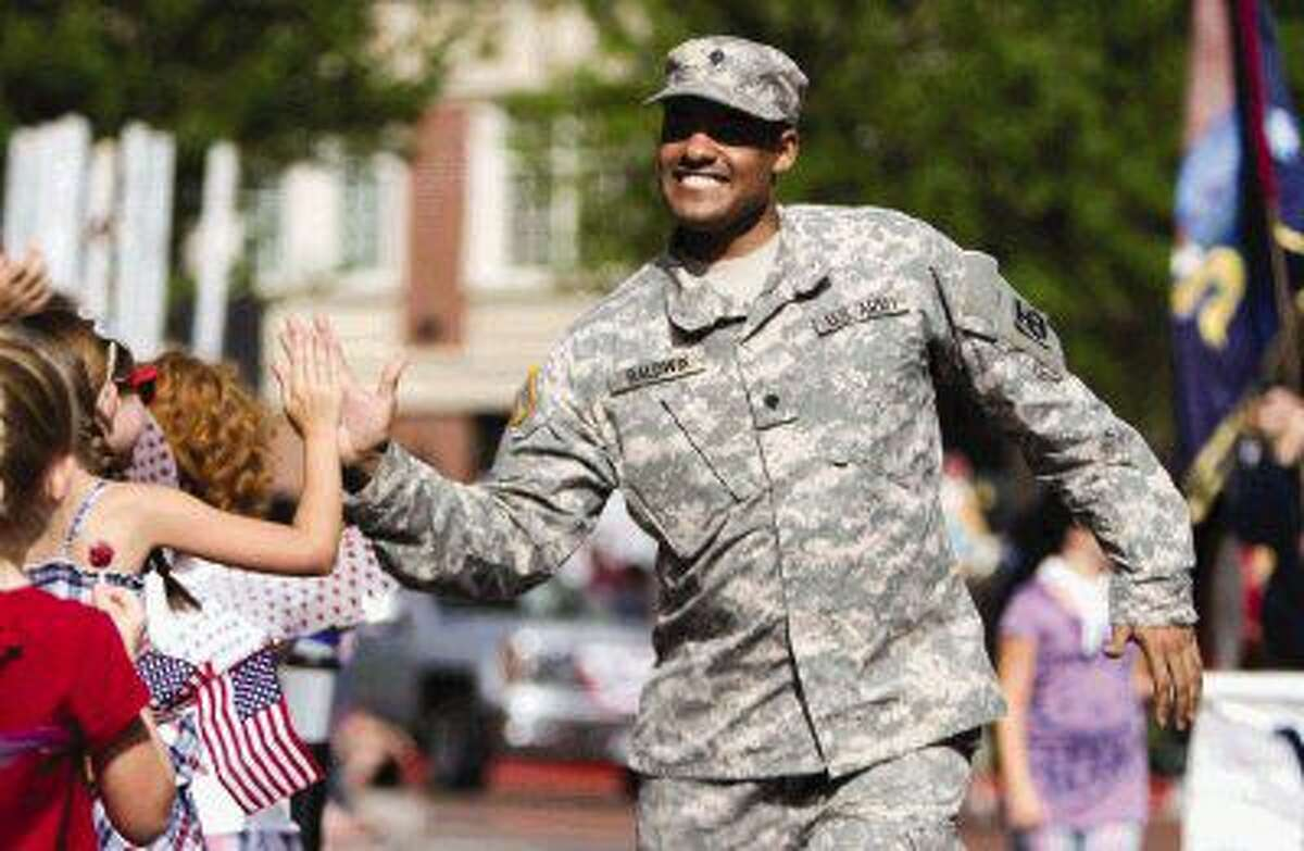 A soldier in the United States Army gives the crowd high-fives during the South County Fourth of July Parade on July 4, 2015 at Market Street.