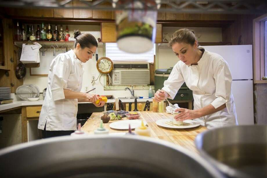 Executive chef Stacy Crowe-Simonson, right, plates the Blue Crab Tower as pastry chef Joanie Woelfel constructs a Grand Marnier Mousse with Fresh Berries at Chez Nous on Dec. 5, 2014, in Humble. Photo: ANDREW BUCKLEY