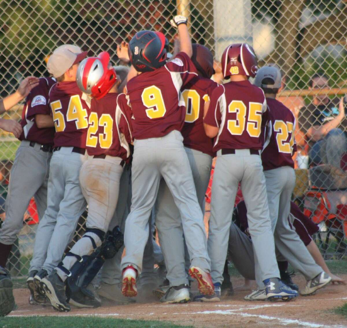 The Deer Park Bronco Gold All-Stars mob Benjamin Gutierrez at home plate after he hit a three-run homer in the third inning against Crosby Friday night. The team clinched a regional berth Saturday with another win over Crosby.