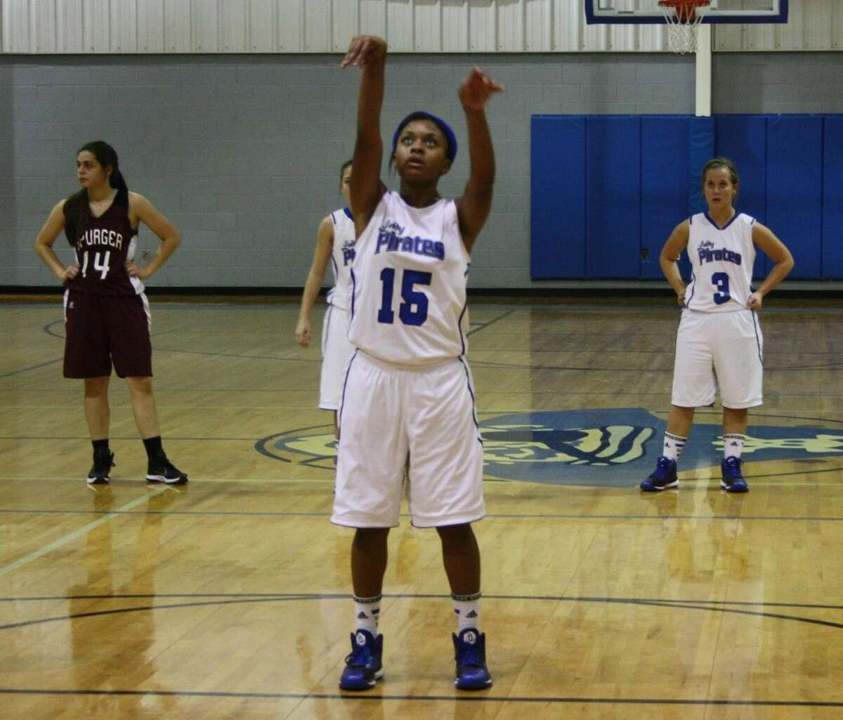 LaQuencia Martin (15) makes a free throw while Maddy McKithan (3) and Cassidy LeBouef (14) stand in place behind her.