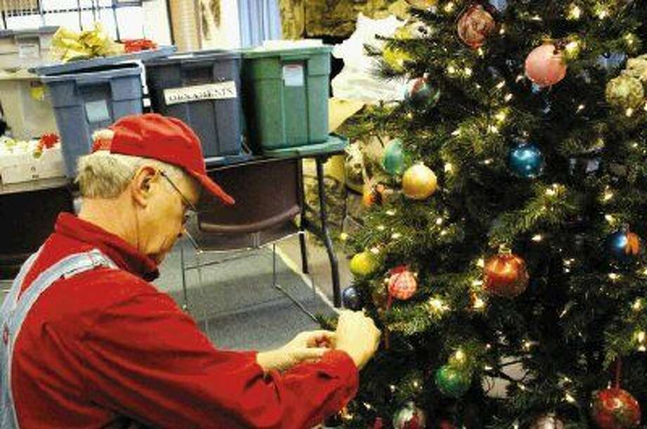 Mercer Volunteer Jim Shotton puts the finishing touches on one of the Christmas trees at Mercer Botanic Gardens.