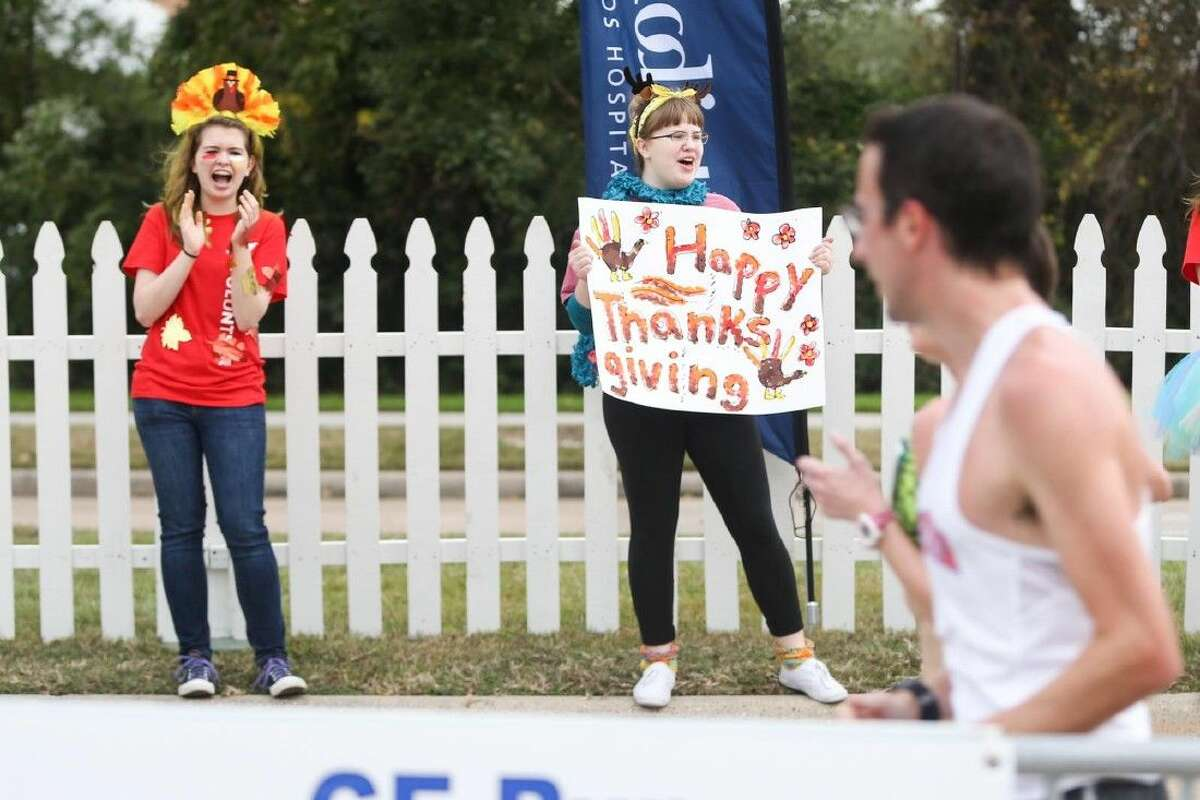 Attendees cheer from the sidelines as runners go past during the 26th annual GE Run Thru The Woods Thursday.