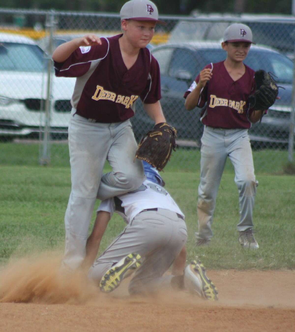 A Pasadena runner dives back to second base as Deer Park shortstop HaydenTronson tries to keep his balance during Sunday's first Section championship game at Spiller Field. Looking on is second baseman Anthony Gabriel.