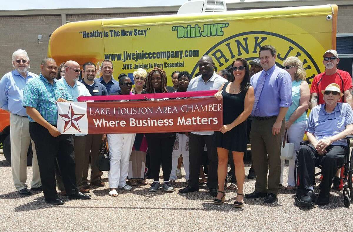 Members of the Lake Houston Area Chamber of Commerce and friends and family of Tamala Austin pose around her JIVE Juice Company van during the ribbon cutting ceremony at the LHACC office in Humble Tuesday, June 5.