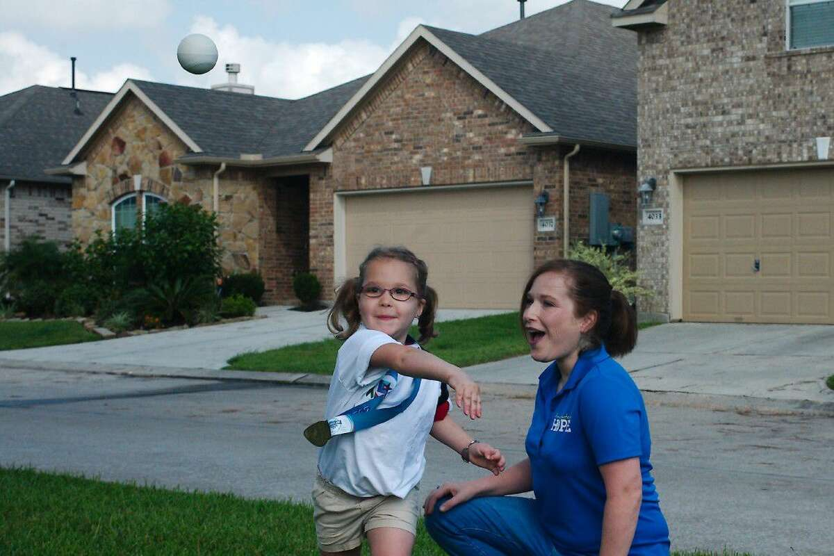 Elise Babin, 4, makes an impressive throw as her mother, Erin, looks on. Elise is a liver transplant recipient.