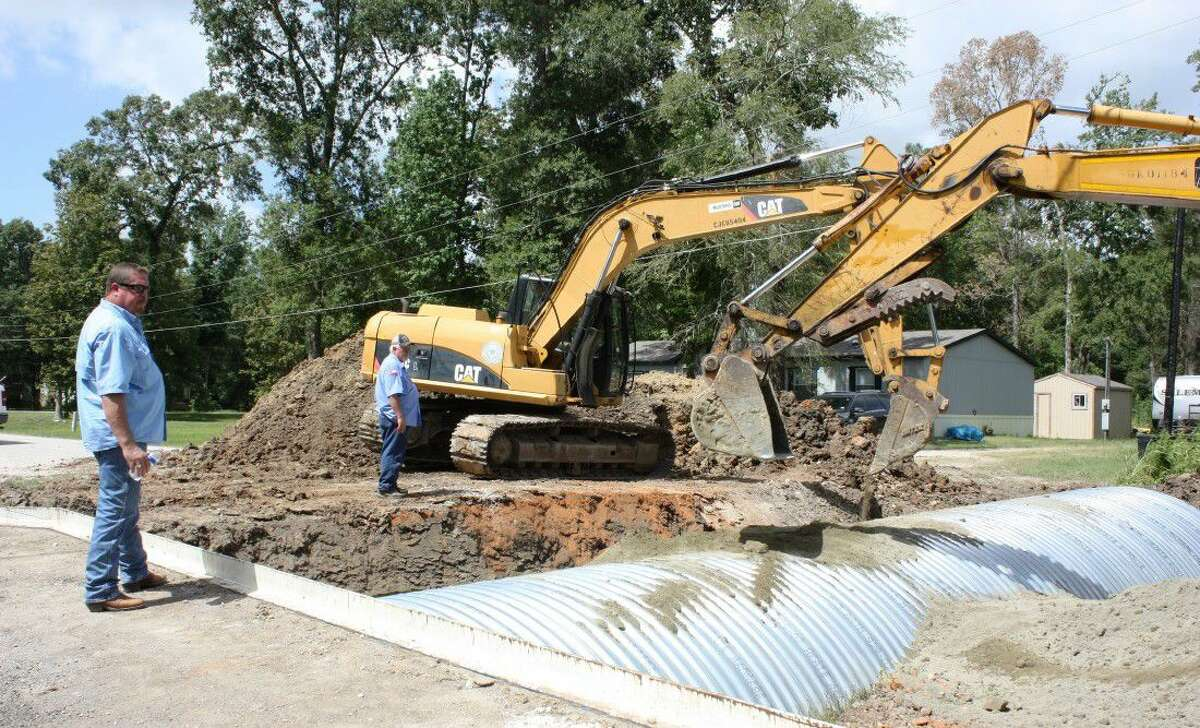Pct. 4 Commissioner Leon Wilson (left) oversees the installation of a new culvert on CR 67631 in the Woodland Hills Subdivision in Dayton. The old culvert washed out during the rains in late May.