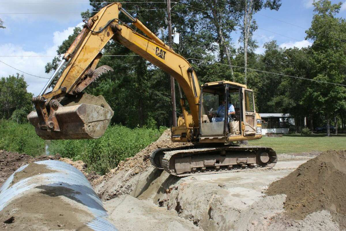 Bob Holon with Pct. 4 Road and Bridge Department applies stabilizing sand to the sides and top of a new culvert on CR 67631 in the Woodland Hills Subdivision.