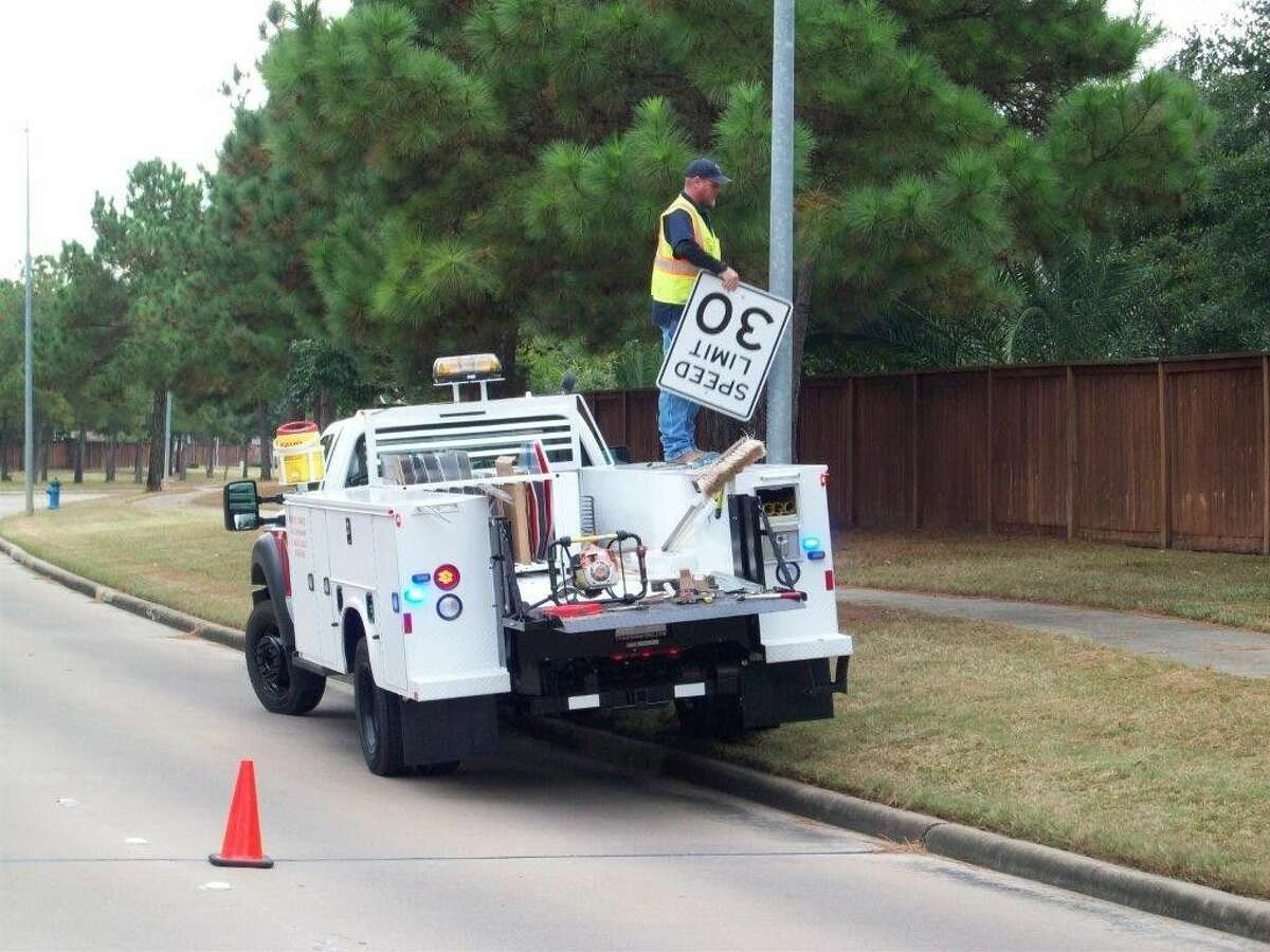 Precinct 4 employee Danny Pipes installs a 30 mph speed limit signs on TC Jester Boulevard.
