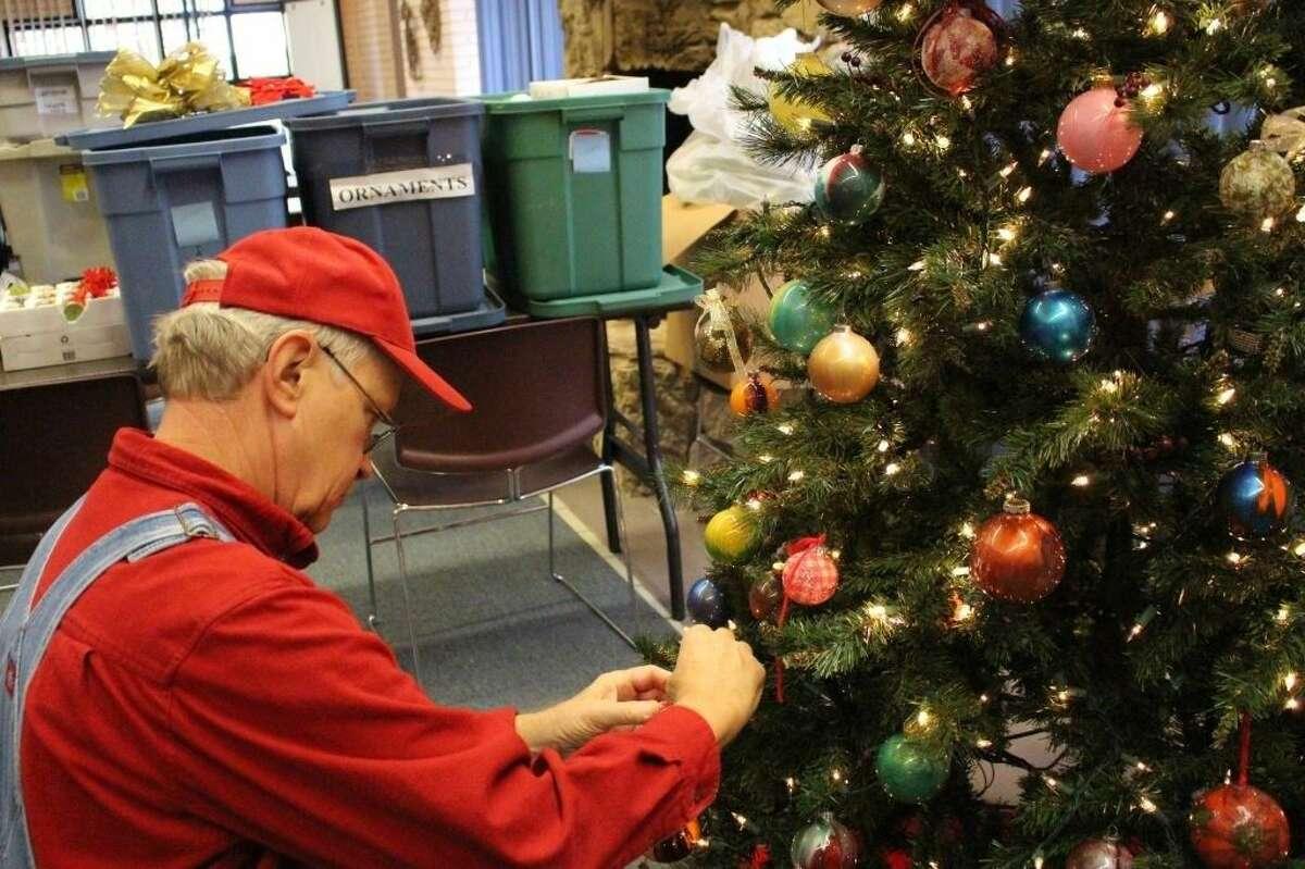 Mercer Volunteer Jim Shotton puts the finishing touches on one of the Christmas trees at Mercer Botanic Gardens.