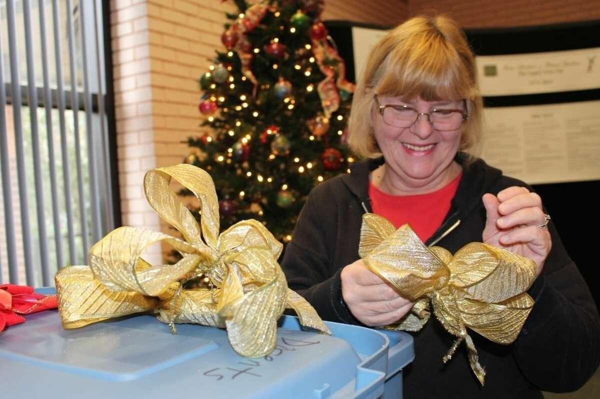 Mercer volunteer Michele Shotton arranges gold tree bows.