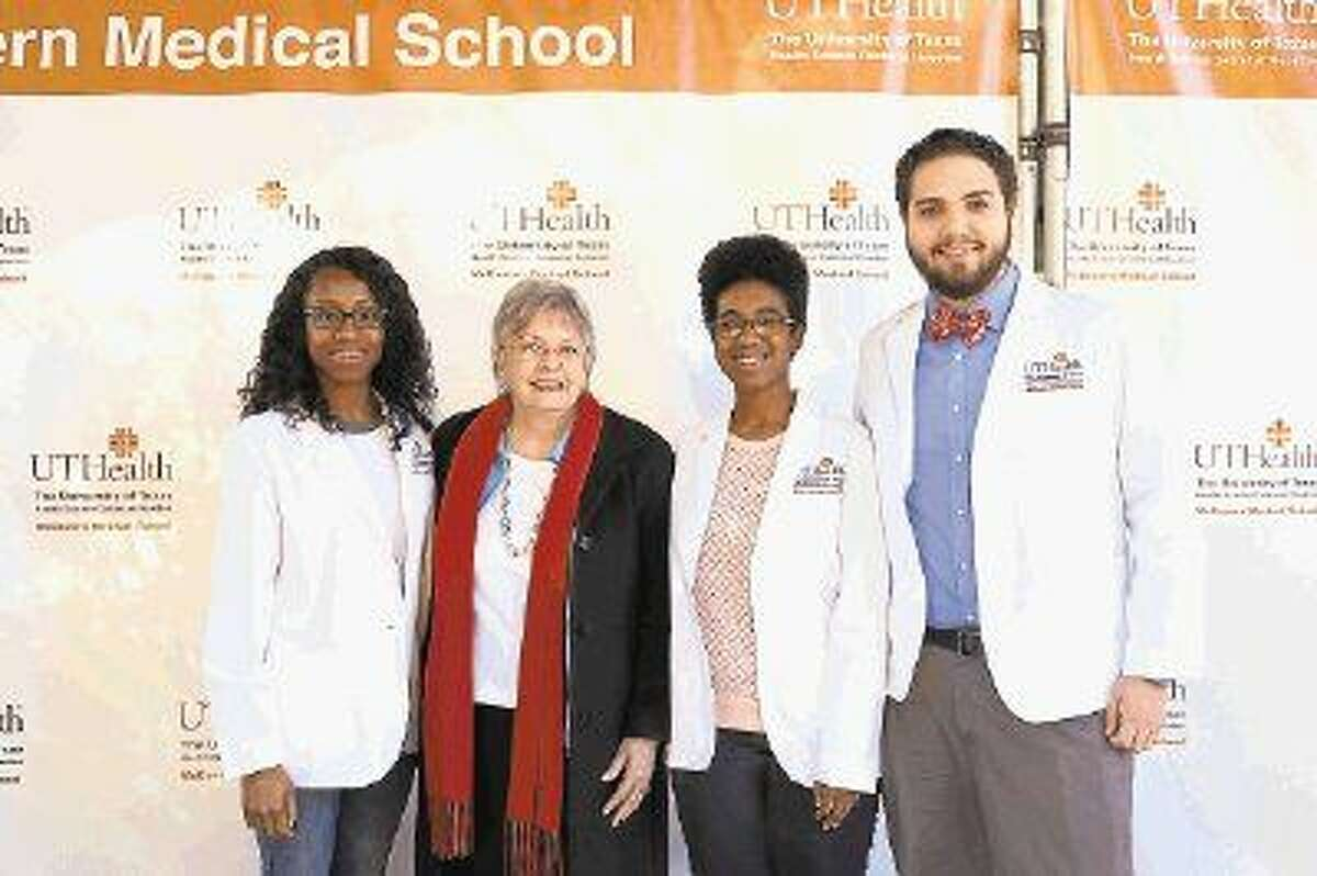 McGovern scholarship student Esther Osuji, Katherine G. McGovern, and McGovern scholarship students Elzia Broussard and Matthew Forster. The students are wearing new lab coats with McGovern Medical School on them.