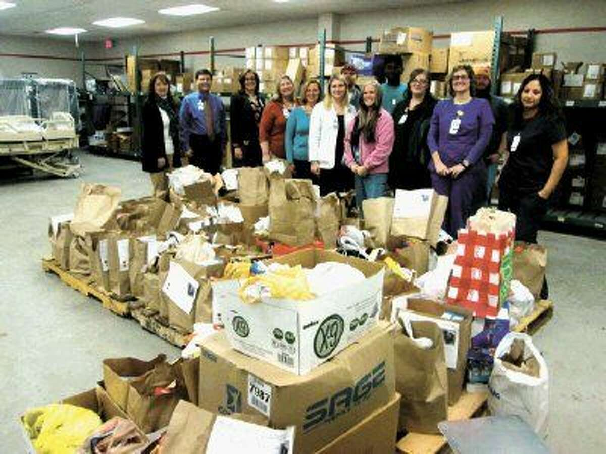 Humble Area Assistance Ministries (HAAM) executive director Millie Garrison (far left) joined Memorial Hermann Northeast CEO Louis Smith (second from left) and members of the Hospital's Partners in Caring (PIC) Team in raising almost 10,000 pounds of food and cash for HAAM's annual Season of Sharing Food Drive.