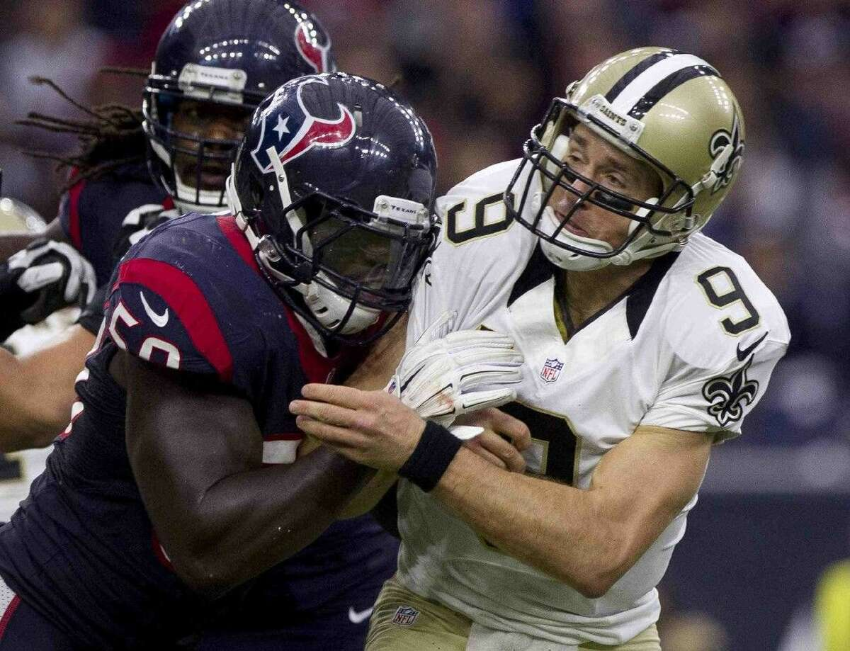 Texans linebacker Akeem Dent, left, delivers a hit to New Orleans Saints quarterback Drew Brees on an incomplete pass in Sunday's game.