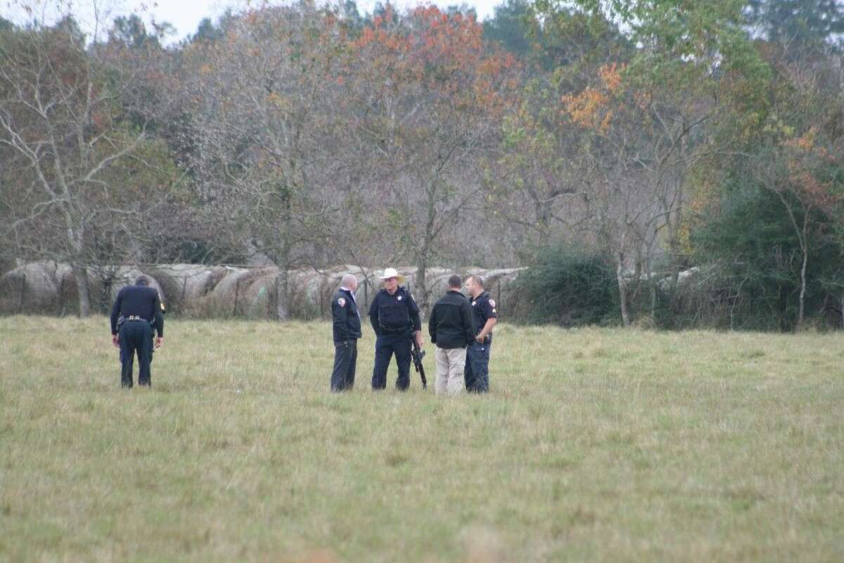 Law enforcement officers look for items left behind by a suicidal man on Tuesday, Dec. 1. The man shot himself in the face in a field off of SH 105 near the intersection with FM 2518 in Tarkington.