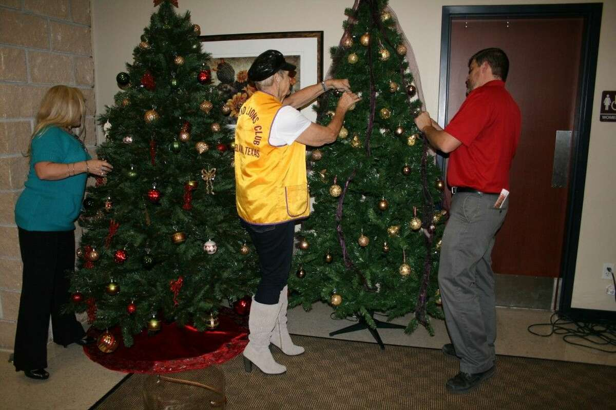 Terrie Manners, Estelle Trevathan and Thomas Higgins work on Christmas trees for the Cleveland Lions Club and Green Bank at the Cleveland Civic Center. The trees are part of this weekend's Hometown Christmas.