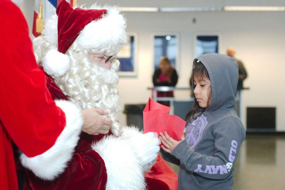 Four-year-old Ysabell Pallo from Children's University offers her letter to Santa at the Pasadena Post Office on Pasadena Blvd. Tuesday, Dec. 2.
