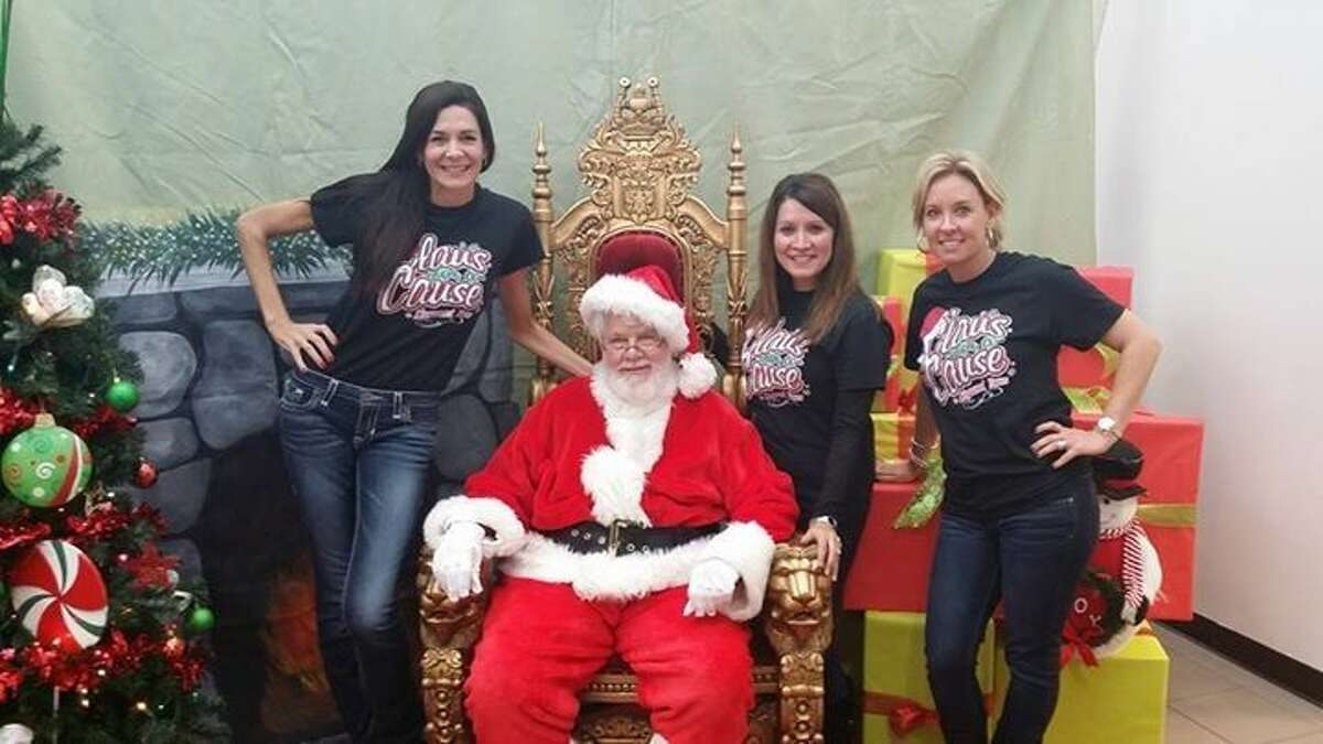 Claus for a Cause volunteers pose with Santa at a previous Claus for a Cause event.