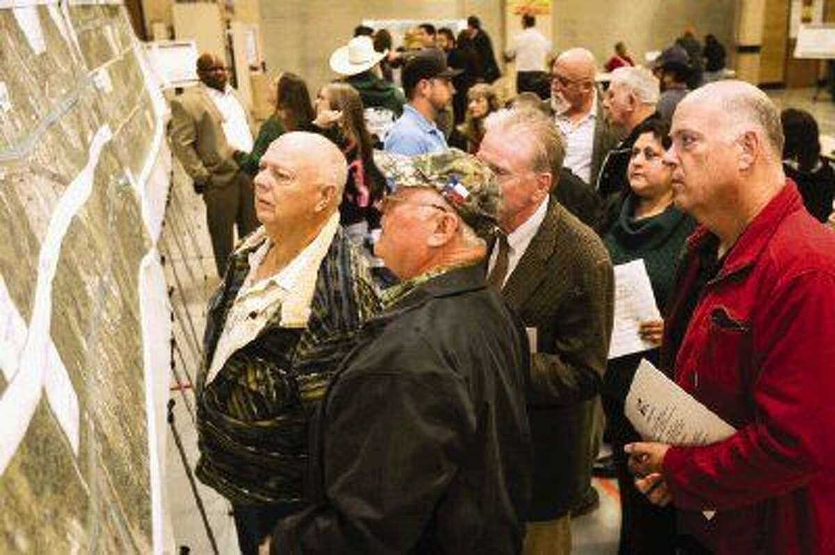 Residents look at print-outs of the TxDOT plans for widening SH 105 during the open house on Tuesday, Dec. 1, at Austin Elementary in Conroe. The project will provide two lanes of travel in either direction from Conroe to Cleveland.