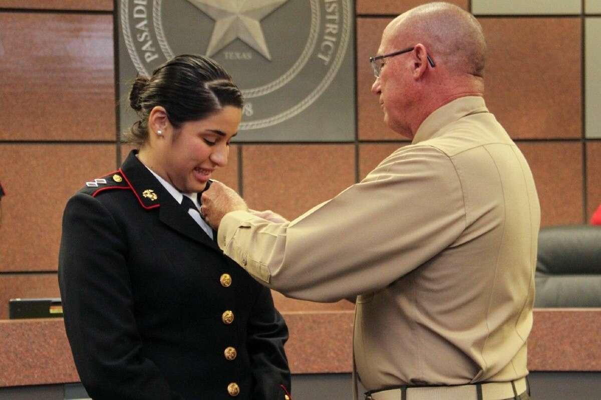Regional ROTC Director Lt. Col. Mark Stroman pins the Legion of Valor of the United States of America Bronze Cross award on Cadet Jasmin Astorga.