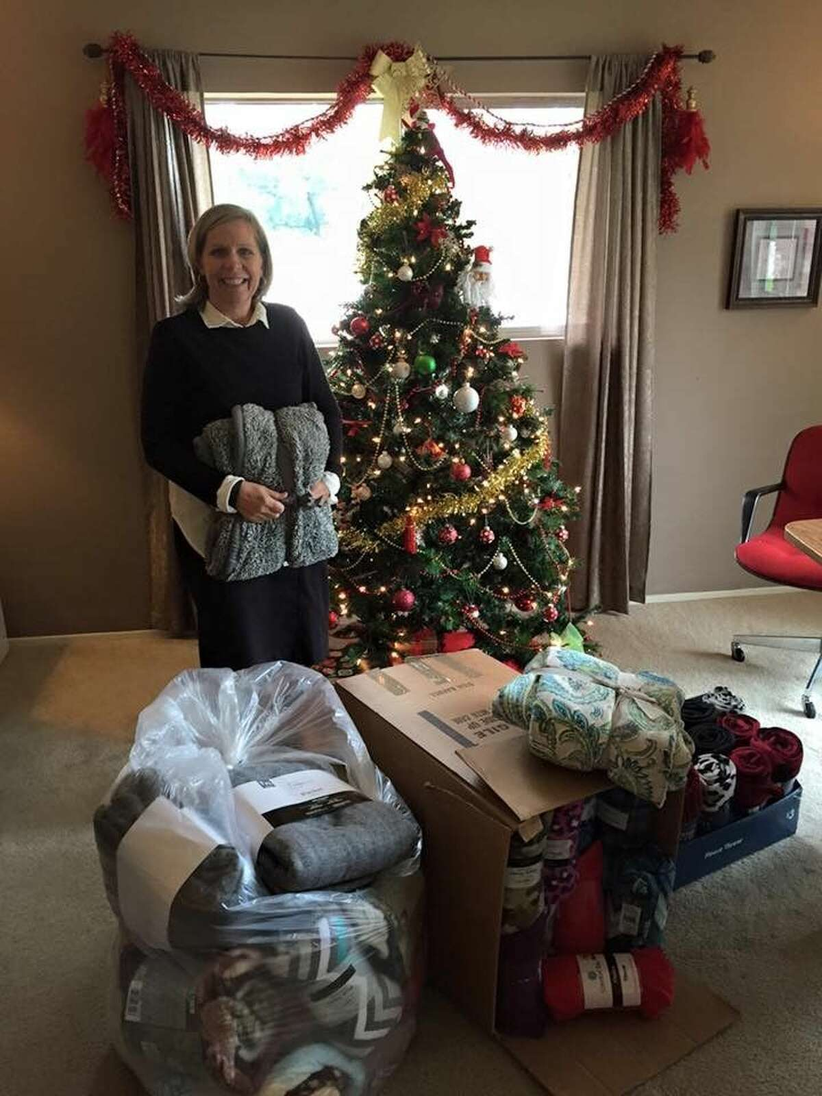 """Family Promise of Lake Houston's Executive Director Carole Brady with donated blankets from """"Page's Blanket Drive."""""""
