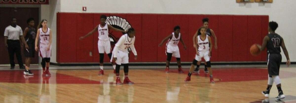The Lady Trojans (left) prepare to defend against an incoming Palestine Lady Cat.