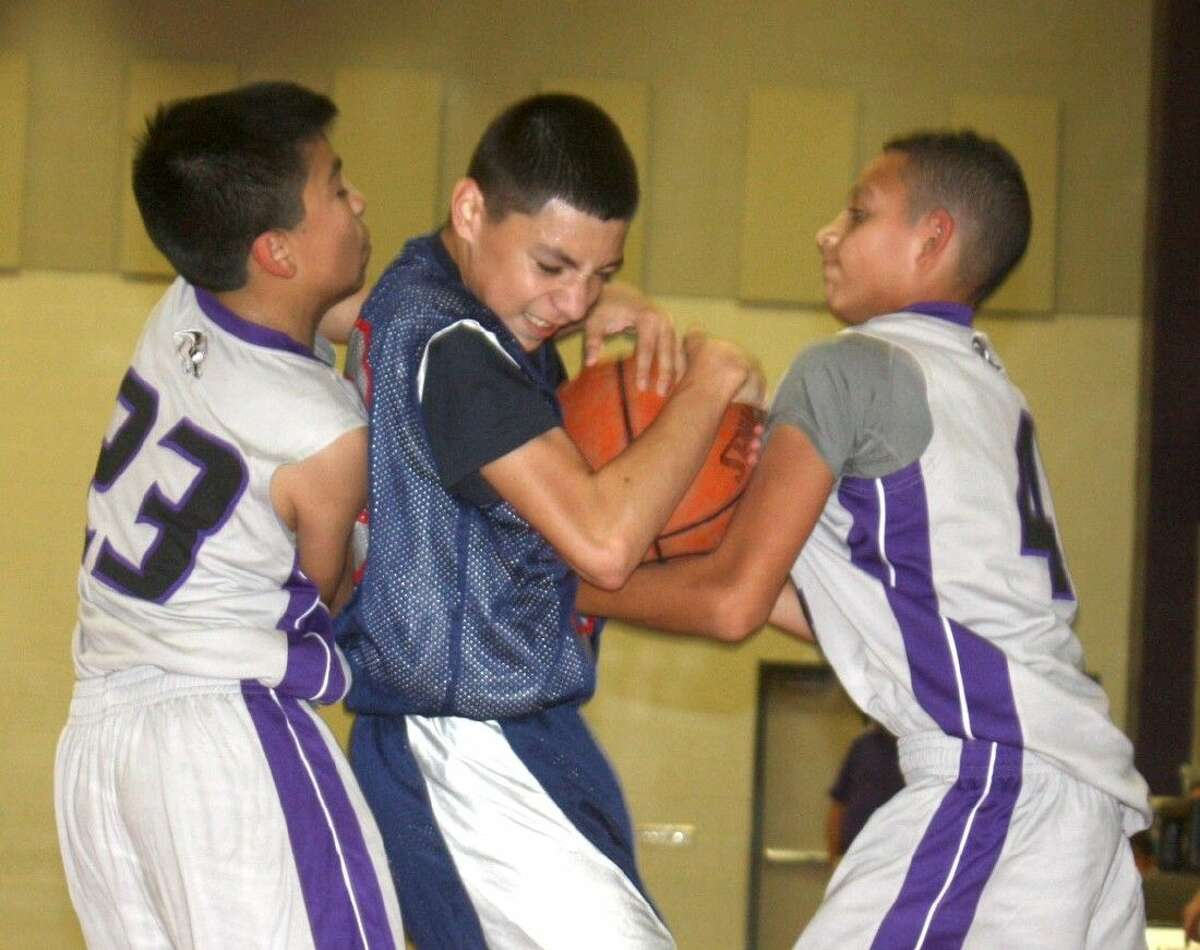 Bondy Intermediate's Elias Castro is sandwiched by Southmore's Javier Carona (23) and Donovan Berotte as Castro attempts to prevent a jump ball. The Bulldogs were whistled for a foul on the play during second-half action Wednesday night.