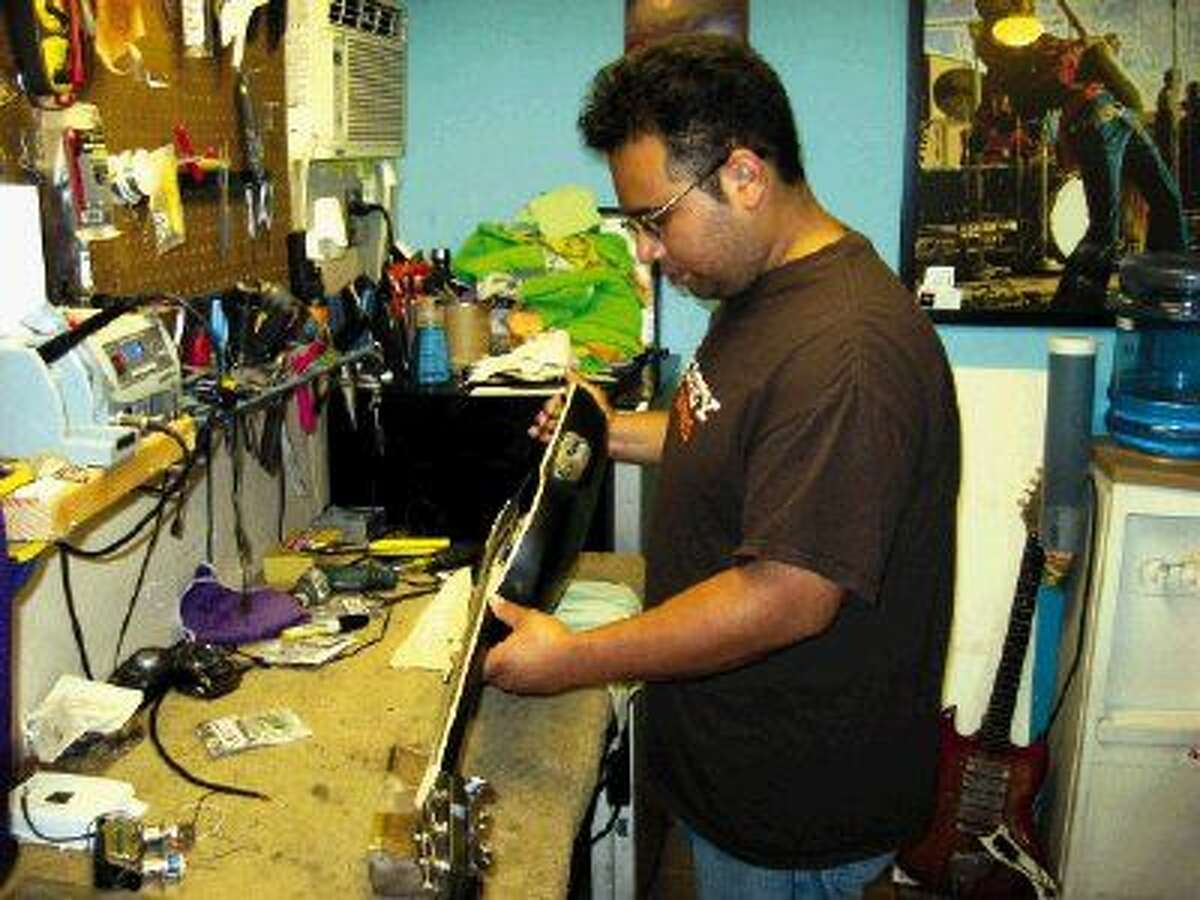 """Daniel """"Booney"""" Carranco works on an Ovation acoustic guitar. Carranco sets up and repairs electric guitars, acoustic guitars and just about any stringed instrument. He also repairs amplifiers in his newly-expanded shop."""