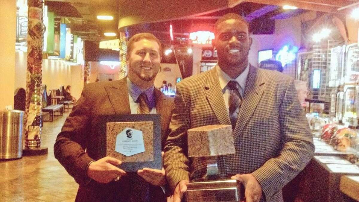 Westfield offensive line coach Justin Outten and Toby Weathersby pose with trophies after winning the Lombardi Award.