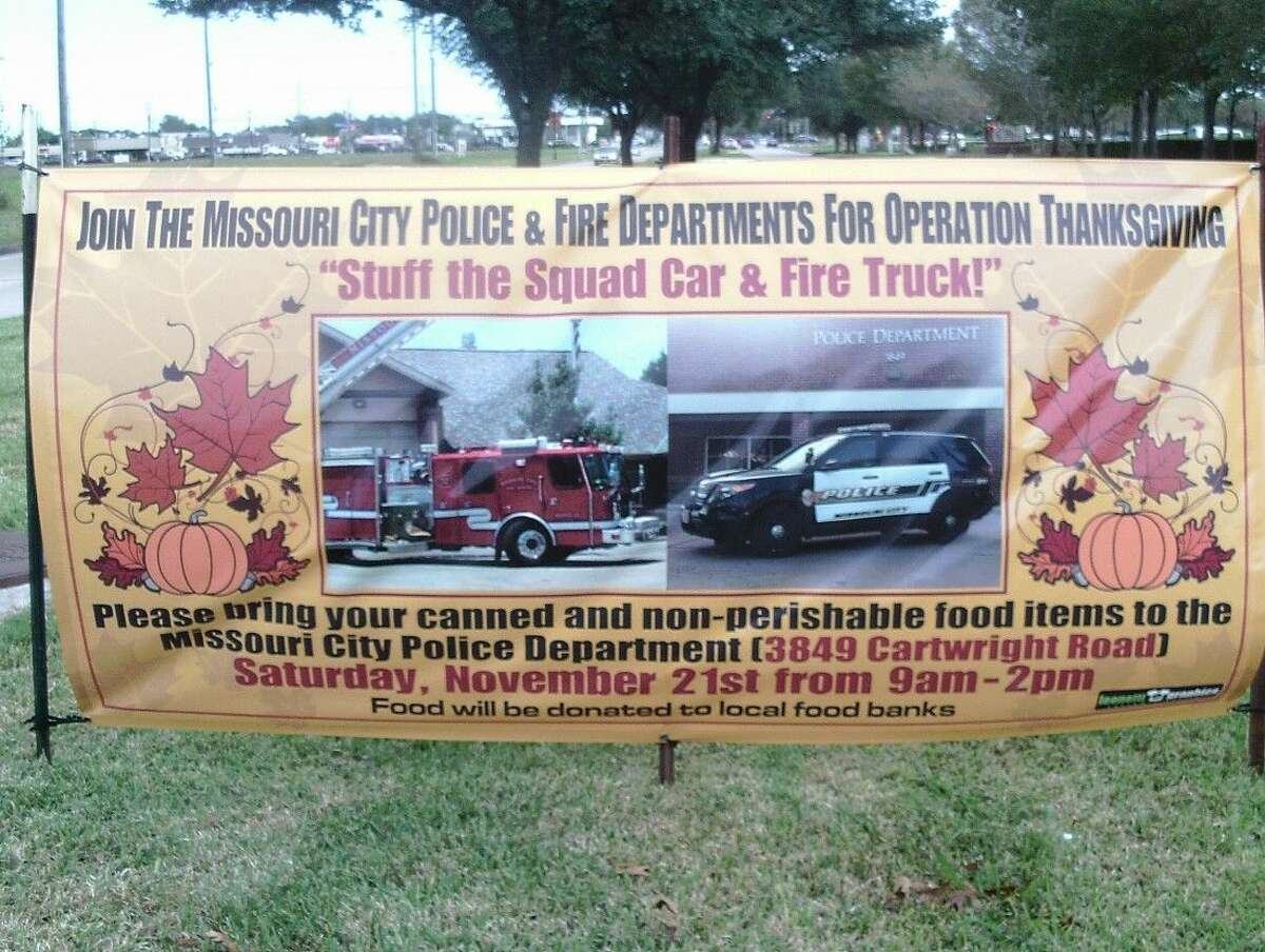 """Banners advertising the """"Stuff the Squad Car and Fire Truck"""" food drive invited the public to drop off canned goods to help others."""