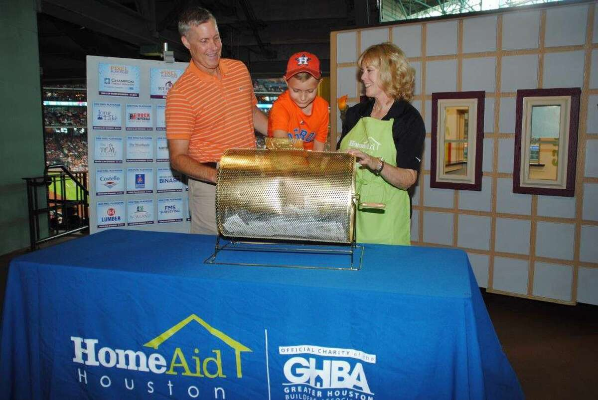 Jay McManus, president of the Houston Division of M/I Homes, holds his son Jake, age 6, as he picks the winner of a fanciful playhouse in the 2016 HomeAid Project Playhouse fundraiser, cheered him on by Bette Moser, executive director of HomeAid Houston. The winner was GHBA Kimberley Cook and her family.