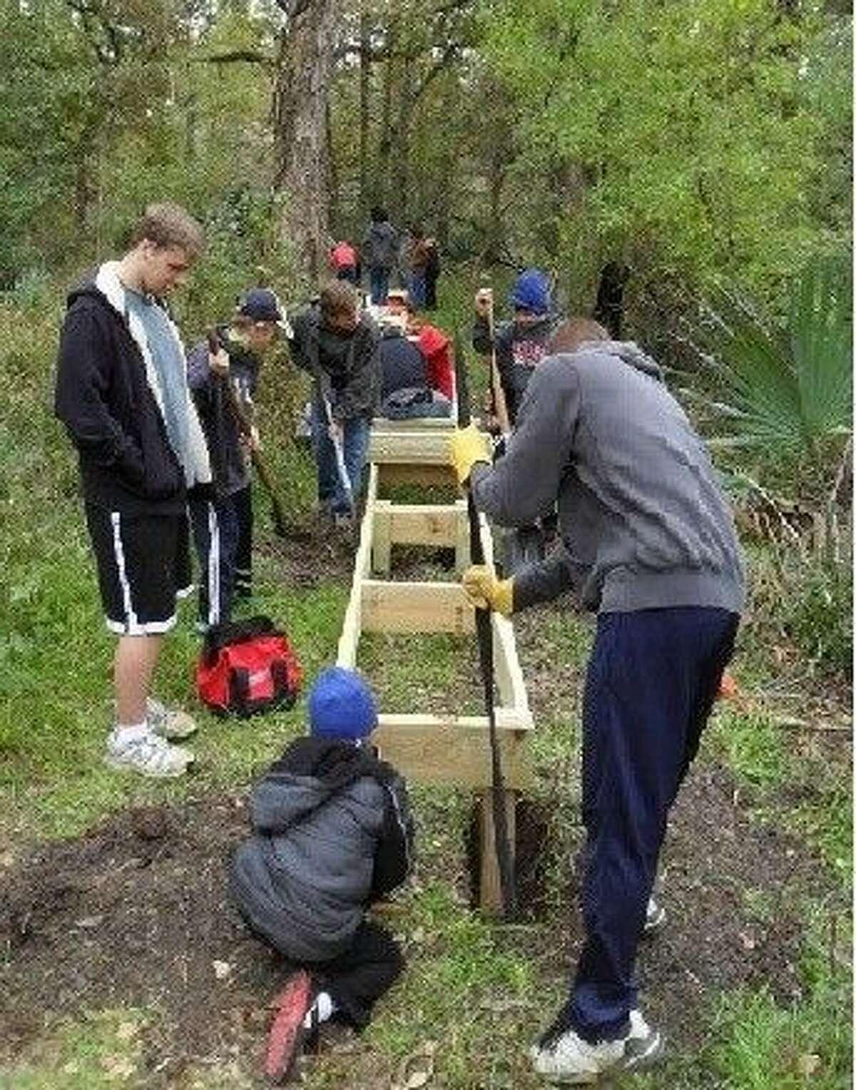Magnolia area Boy Scouts work on a boardwalk at Montgomery County Lake Creek Preserve.