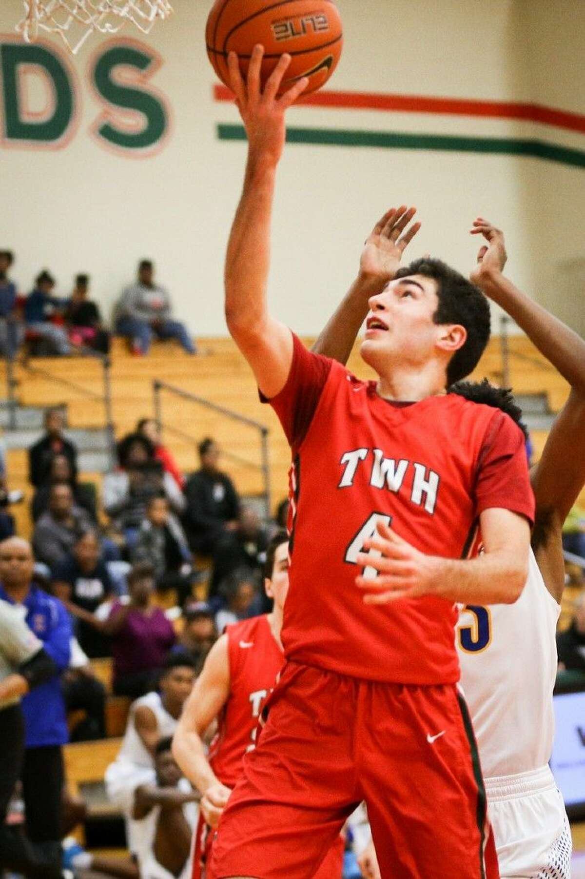 The Woodlands' Kyle Spears (4) goes for a layup during a high school boys basketball game against Fort Bend Elkins this past Saturday night.