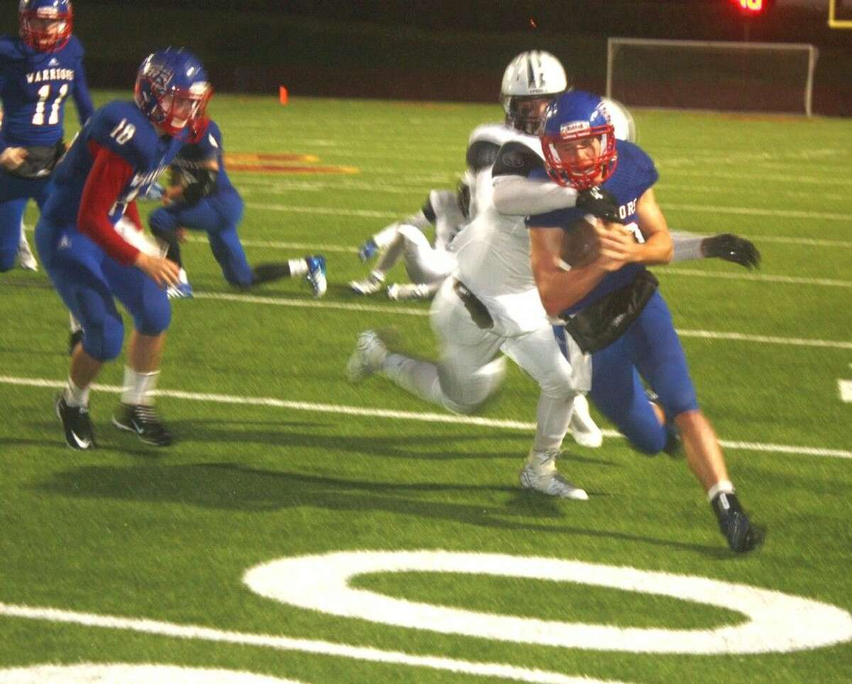 Brett Houston runs for a five-yard gain in the final seconds of the first half, trying desperately to put some padding on a fragile 8-7 Warriors lead. To the left is Christopher Gonzalez.