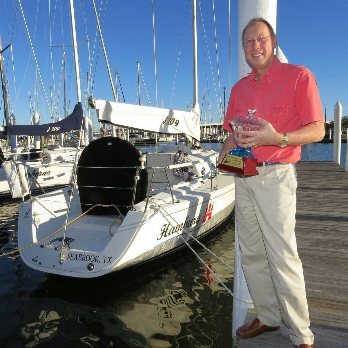 """Lakewood Yacht Club racer Al Goethe holds his """"Yacht of theYear"""" award alongside his J/105 """"Hamburg"""" which captured the award at the club's Fall Ball and Awards Ceremony held recently."""