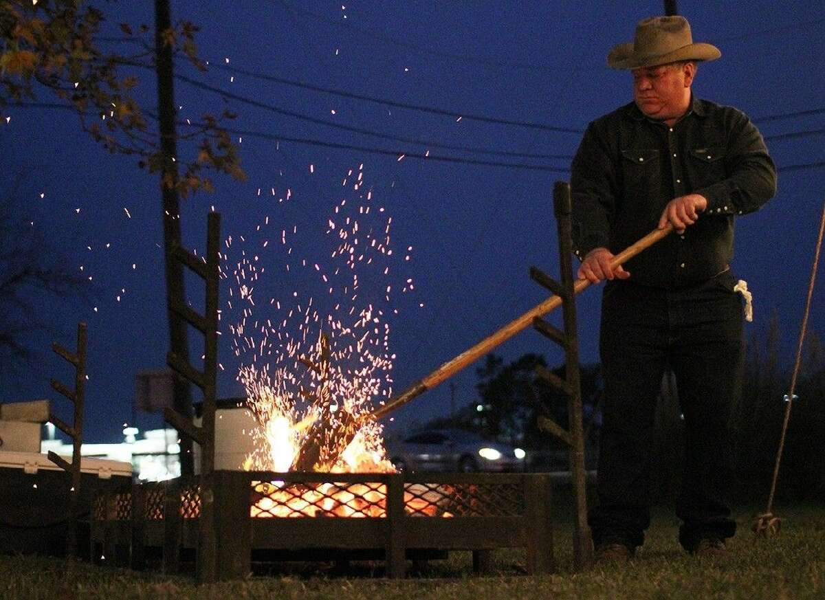 Pat Wood, of the Buck Reams and the Chuckwagon Cookers, stokes the fire during the ACC Foundation Christmas Gala on December 2.