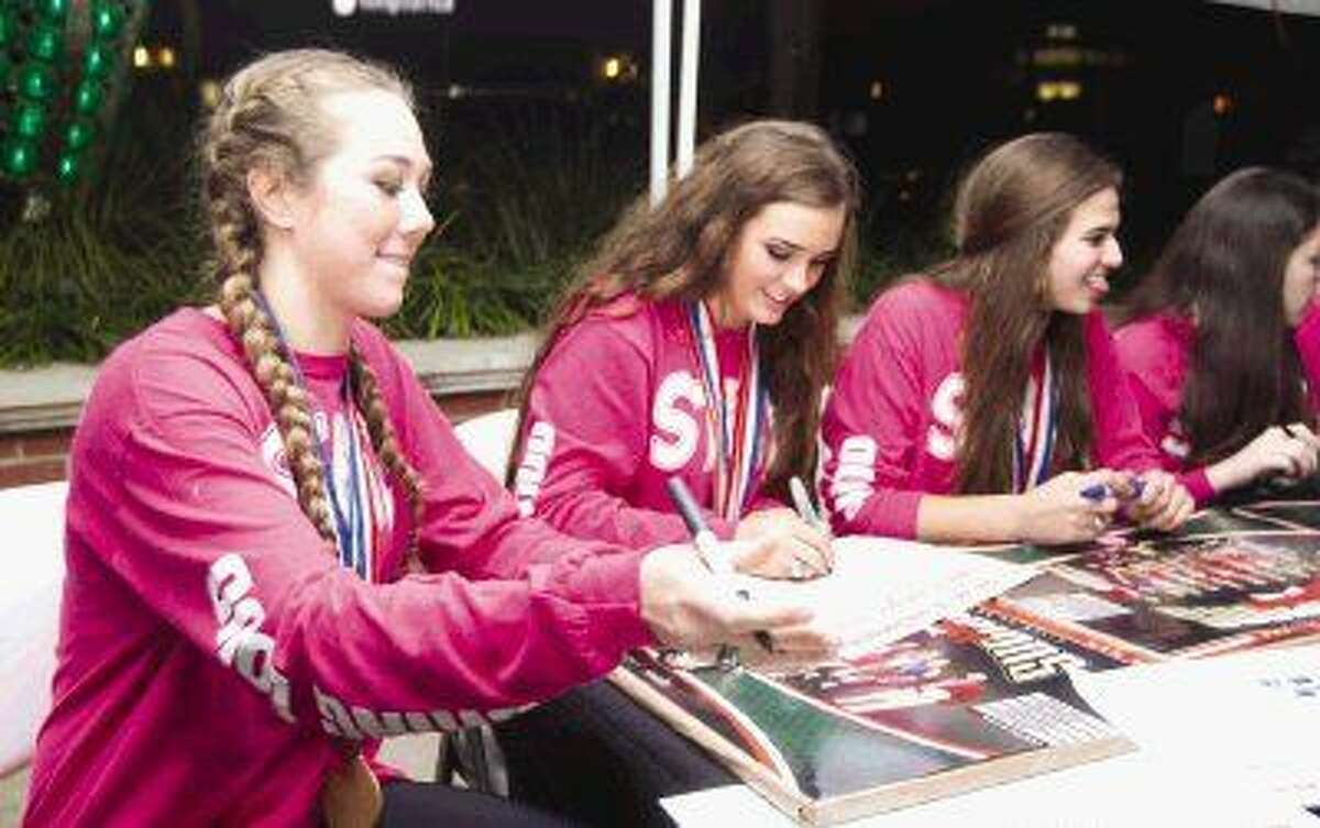 The Woodlands volleyball players Julia Pasch, Kendall Cook and Courtney Quinn autograph commemorative posters during a parade in celebration of the program's second straight state volleyball title at Market Street Thursday. To view or purchase this photo and others like it, visit HCNpics.com.