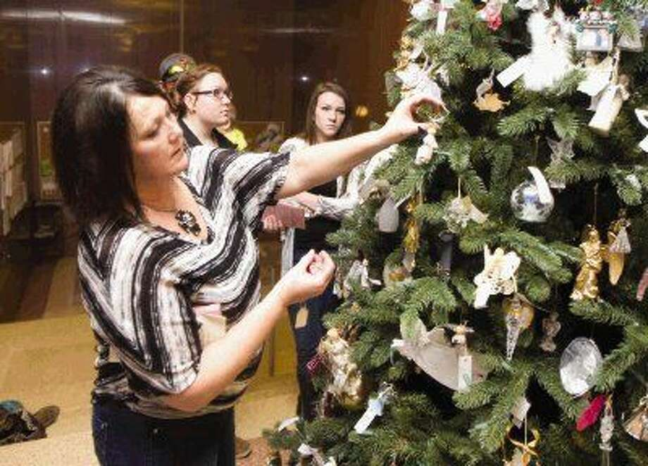 Bobbie Oldfield hangs an ornament for her sister Carrie Atkinson Allison during the Tree of Angels dedication Thursday at the Montgomery County Courthouse. Photo: Jason Fochtman